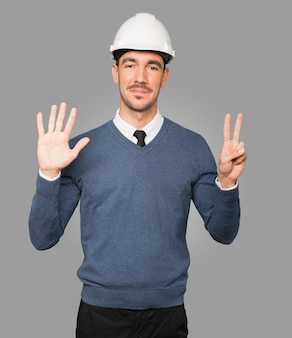 Młody architekt wykonujący gest numer siedem