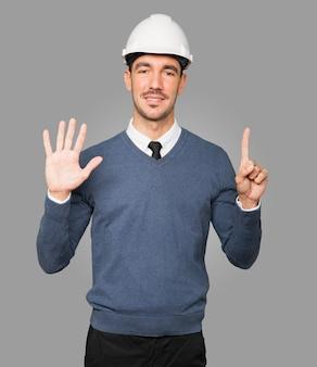 Młody architekt wykonujący gest numer sześć