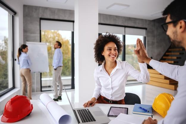 Młody architekt żeński rasy mieszanej siedzi w biurze i daje piątkę swojemu koledze. w tle jest więcej architektów pracujących nad projektem.
