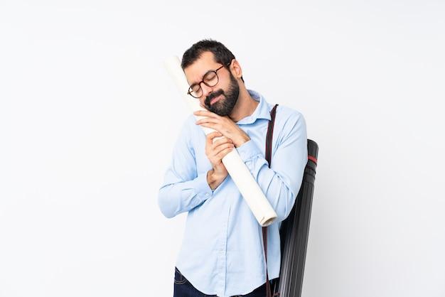 Młody architekta mężczyzna z brodą nad odosobnionym bielem robi sen gestowi w dorable wyrażeniu