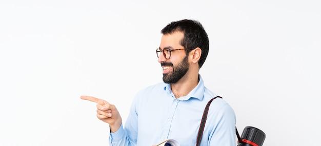 Młody architekta mężczyzna z brodą nad odosobnionym bielem wskazuje z boku przedstawiać produkt