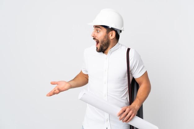 Młody architekta mężczyzna z hełma i mienia projektami odizolowywającymi na biel ścianie z niespodzianki wyrażeniem podczas gdy patrzejący stronę