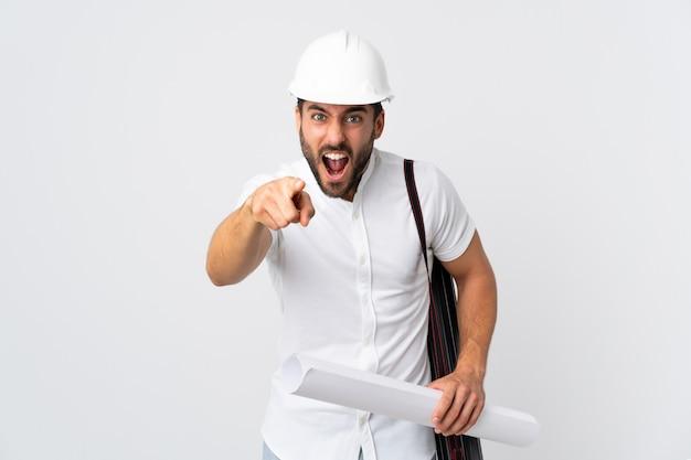 Młody architekta mężczyzna z hełmem i mienia projektami odizolowywającymi na biel ścianie udaremniał i wskazuje przód