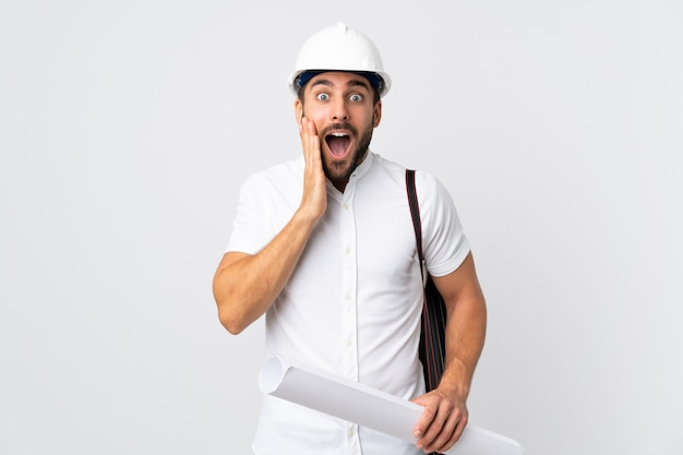 Młody architekta mężczyzna z hełmem i mienie projekty odizolowywający na biel ścianie z niespodzianką i szokującym wyrazem twarzy