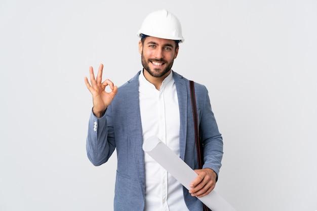 Młody architekta mężczyzna z hełmem i trzymający projekty odizolowywający na biel ścianie pokazuje ok znaka z dwiema rękami