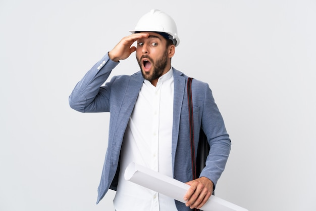 Młody architekta mężczyzna z hełmem i trzymający projekty odizolowywający na bielu robi niespodzianka gestowi podczas gdy patrzejący strona