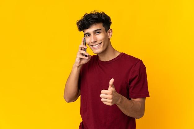 Młody argentyńczyk na białym tle na żółtym tle, prowadząc rozmowę z telefonem komórkowym, robiąc kciuk do góry