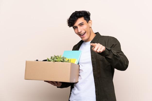 Młody argentyńczyk poruszający się w nowym domu nad odosobnionymi punktami palcem na ciebie z pewnym siebie wyrazem twarzy