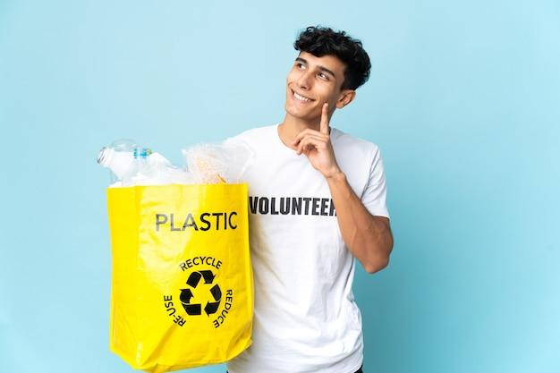 Młody argentyńczyk trzyma torbę pełną plastiku, myśląc o pomyśle, patrząc w górę