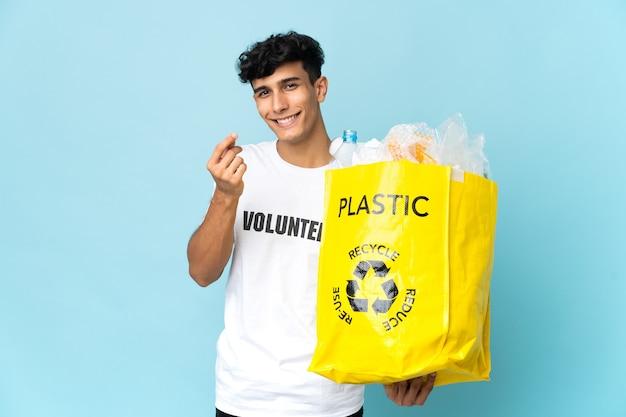 Młody argentyńczyk trzyma torbę pełną plastiku, zarabianie pieniędzy gestem