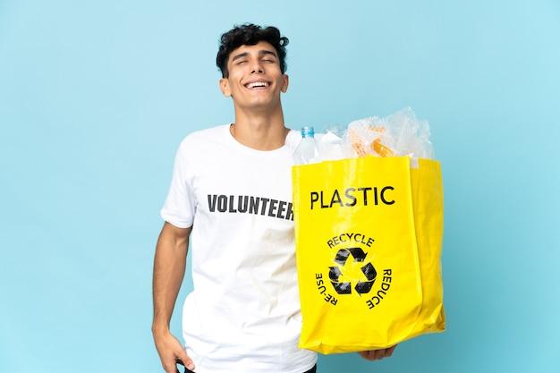 Młody argentyńczyk trzymając torbę pełną plastiku, śmiejąc się