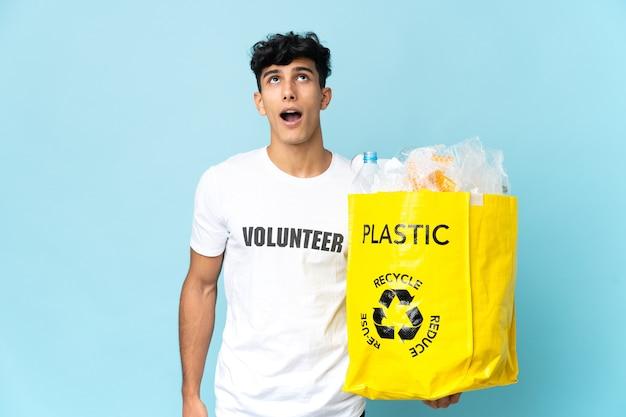 Młody argentyńczyk trzymający torbę pełną plastiku, patrząc w górę i ze zdziwieniem