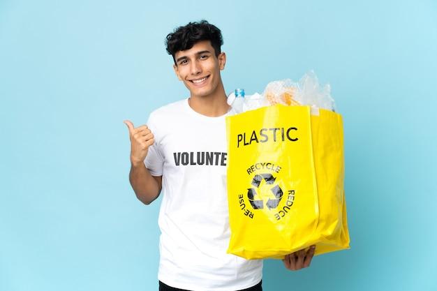 Młody argentyńczyk trzymający torbę pełną plastiku, wskazujący w bok, aby zaprezentować produkt