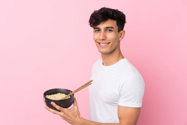 Młody argentyńczyk uśmiecha się dużo, trzymając miskę makaronu pałeczkami
