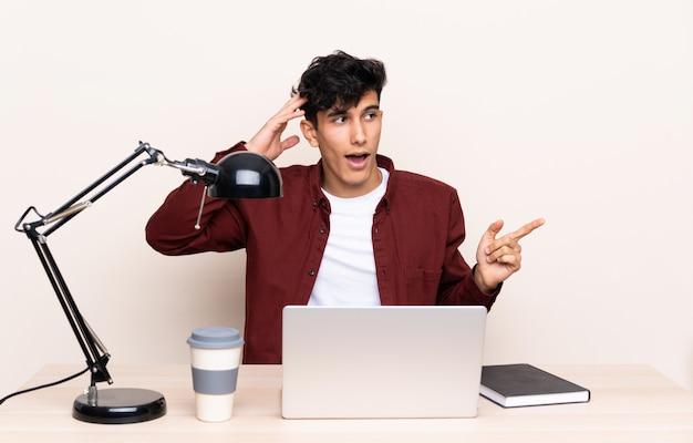 Młody argentyńczyk w stole z laptopem w swoim miejscu pracy zaskoczony i wskazujący palec na bok