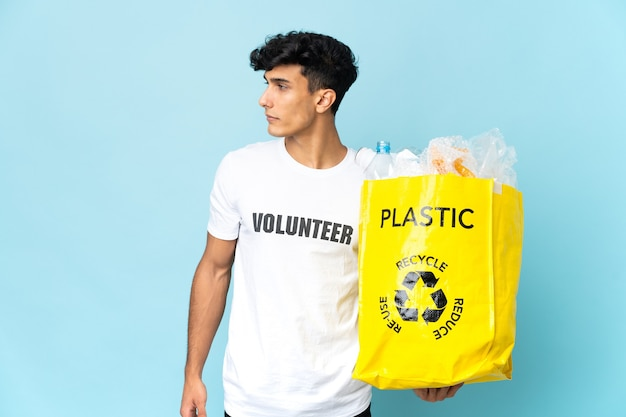 Młody argentyńczyk z torbą pełną plastiku, patrząc z boku
