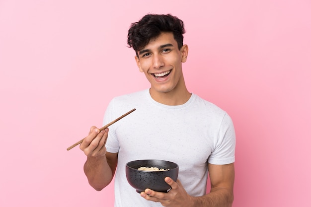 Młody argentyński mężczyzna nad odosobnioną biel ścianą trzyma puchar kluski z pałeczkami