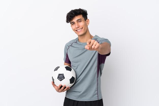 Młody argentyński mężczyzna nad odosobnioną biel ścianą z piłki nożnej piłką i wskazywać z przodu