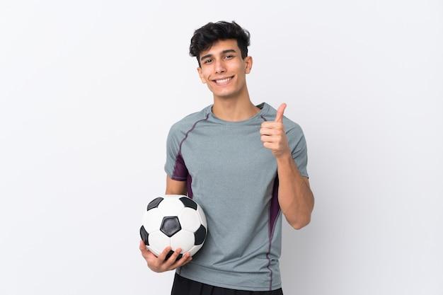 Młody argentyński mężczyzna nad odosobnioną biel ścianą z piłki nożnej piłką z kciukiem up i