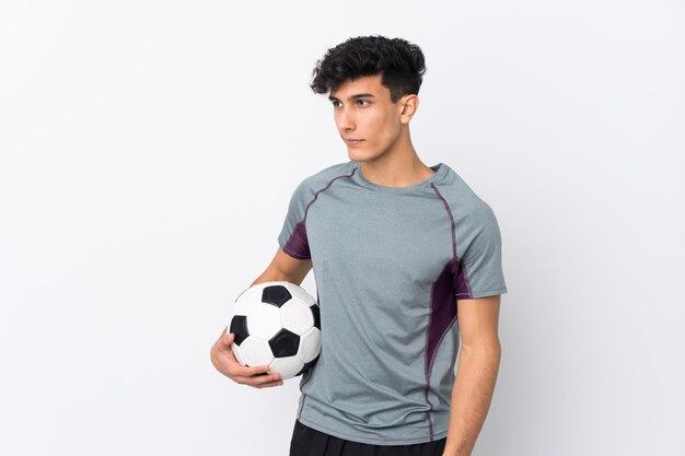 Młody argentyński mężczyzna nad odosobnioną biel ścianą z piłki nożnej piłką