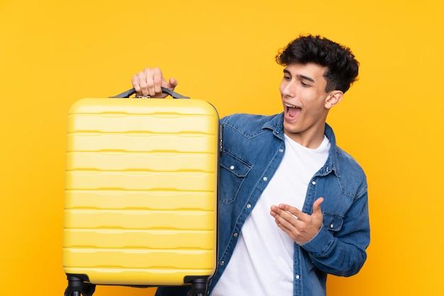 Młody argentyński mężczyzna nad odosobnionym żółtym tłem w wakacje z podróży walizką
