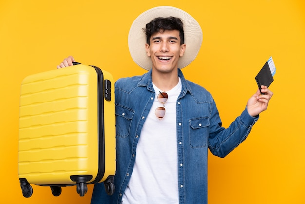 Młody argentyński mężczyzna nad odosobnionym żółtym tłem w wakacje z walizką i paszportem i zaskakujący