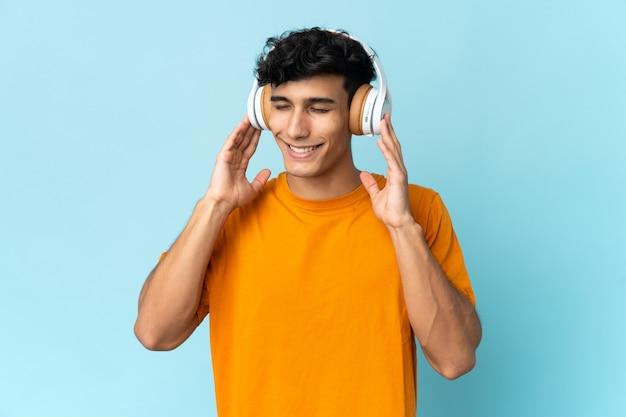 Młody argentyński mężczyzna odizolowany na tle słuchania muzyki