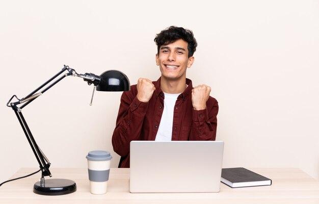 Młody argentyński mężczyzna świętuje zwycięstwo w stole z laptopem w jego miejscu pracy