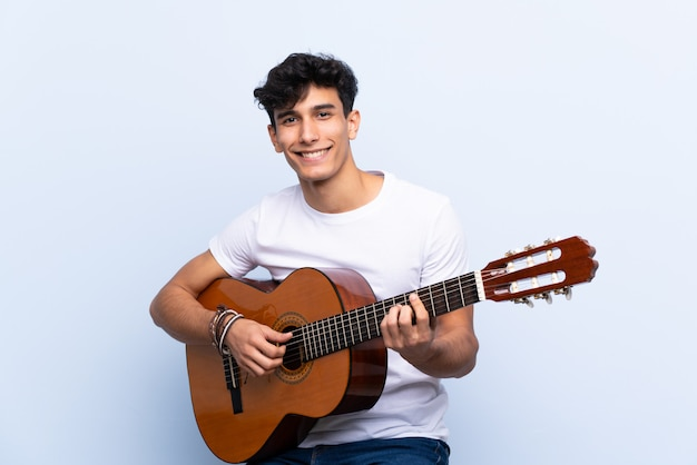 Młody argentyński mężczyzna uśmiecha się dużo z gitarą nad odosobnioną błękit ścianą
