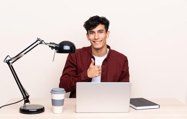 Młody argentyński mężczyzna w stole z laptopem w jego miejscu pracy daje aprobata gestowi