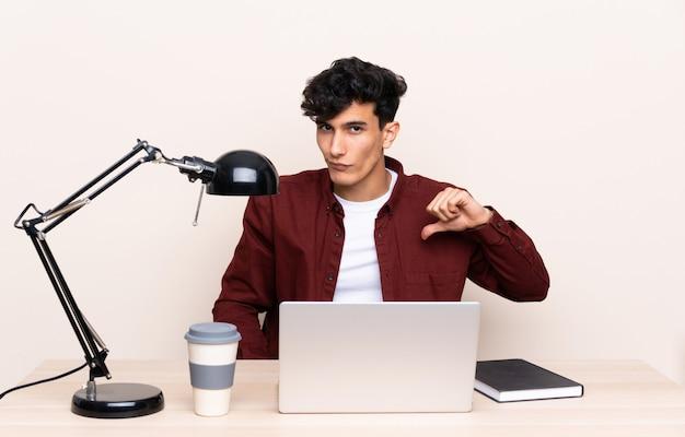 Młody argentyński mężczyzna w stole z laptopem w jego miejscu pracy pokazuje kciuka puszka znaka