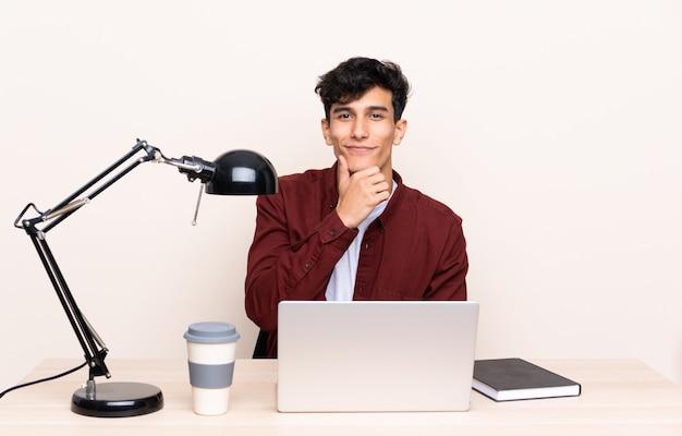 Młody argentyński mężczyzna w stole z laptopem w swoim miejscu pracy śmiejąc się