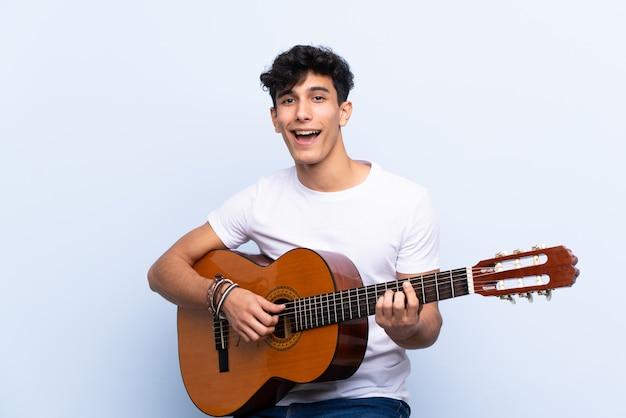 Młody argentyński mężczyzna z gitarą nad odosobnioną błękit ścianą świętuje zwycięstwo