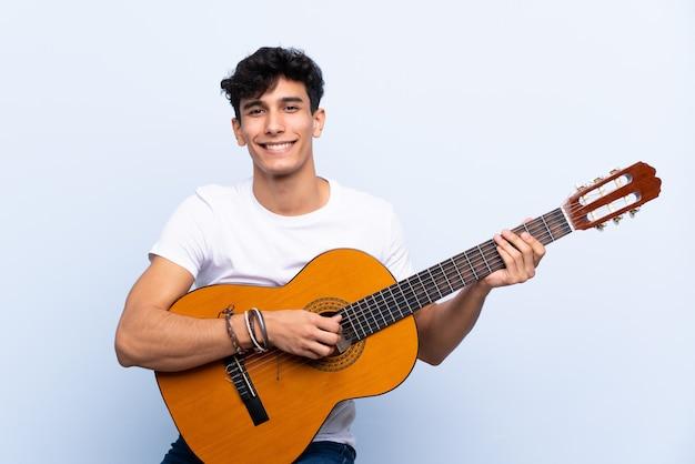 Młody argentyński mężczyzna z gitarą nad odosobnioną błękit ścianą