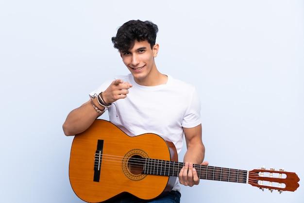 Młody argentyński mężczyzna z gitarą nad odosobnionymi błękitnymi punktami ściennymi dotyka ciebie z ufnym wyrażeniem