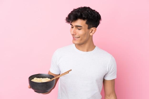 Młody argentyński mężczyzna z szczęśliwym wyrazem, trzymając miskę makaronu pałeczkami