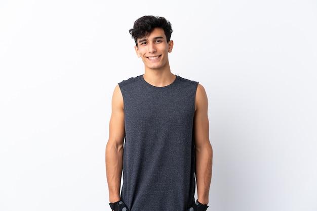 Młody argentyński sporta mężczyzna nad odosobnioną biel ścianą szczęśliwą i uśmiechniętą
