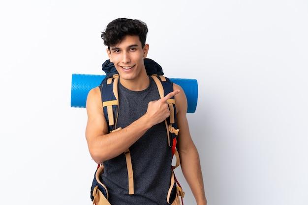 Młody argentyński wycieczkowicz mężczyzna nad odosobnionym biel ściany wskazuje palcem strona
