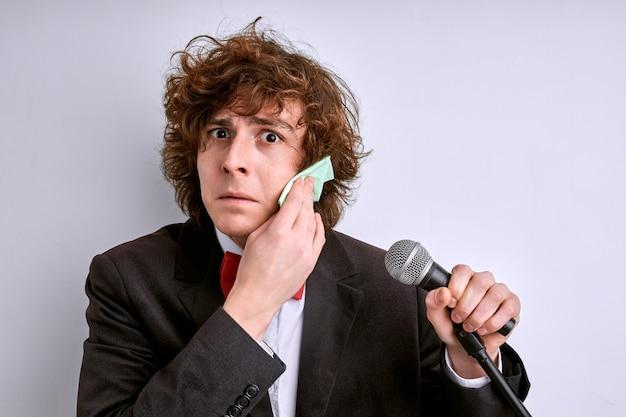 Młody artysta boi się pomyłki podczas występu, stoi ocierając pot z czoła, martwi się złym mówieniem, trzymając mikrofon. na białym tle