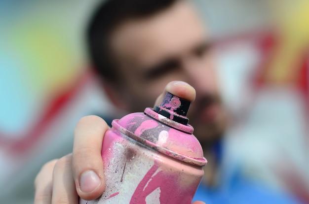 Młody artysta graffiti w niebieskiej kurtce trzyma przed sobą puszkę farby
