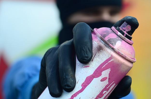 Młody artysta graffiti w niebieskiej marynarce i czarnej masce trzyma przed sobą puszkę farby