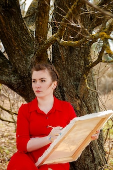 Młody artysta malujący pejzaż. rysuje kobieta w czerwonej sukni siedzi blisko suchego drzewa