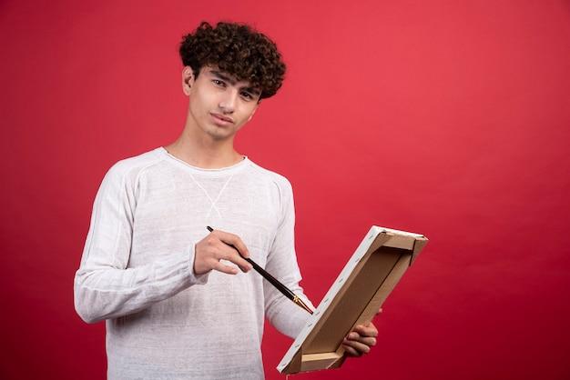 Młody artysta maluje coś na płótnie.