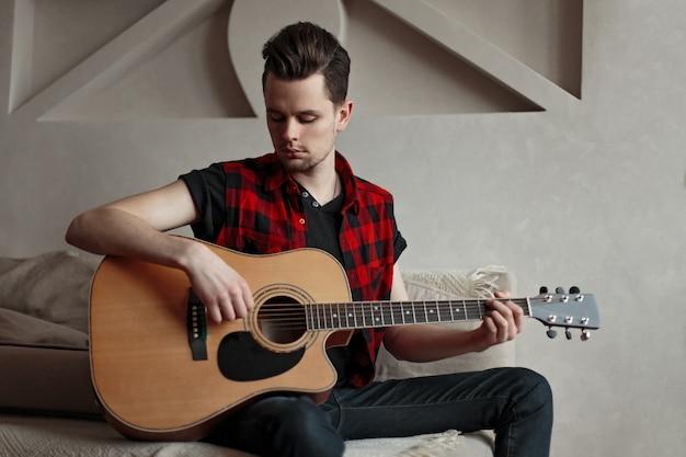 Młody artysta mężczyzna gra na gitarze