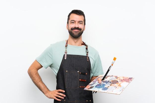 Młody artysta mężczyzna trzyma paletę pozuje z rękami przy biodrem i ono uśmiecha się