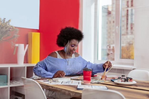 Młody artysta. młody obiecujący artysta trzymający pędzel malarski czuje się natchniony i radosny podczas pracy