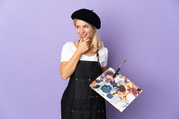Młody artysta rosjanka trzyma paletę na białym tle na fioletowej ścianie, patrząc z boku i uśmiechnięty