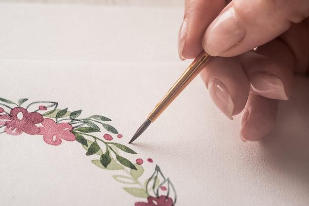 Młody artysta rysuje kwiatu wzór z akwareli farbą i muśnięciem na papierze w miejscu pracy