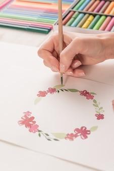 Młody artysta rysuje kwiatu wzór z akwareli farbą i muśnięciem przy miejscem pracy