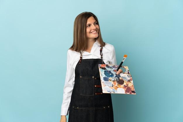Młody artysta słowacka kobieta na białym tle na niebieskiej ścianie, patrząc z boku i uśmiechnięta